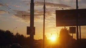 Opinión hermosa de la puesta del sol sobre el camino con tráfico ocupado en la ciudad rusa el tiempo de verano en la cámara lenta metrajes