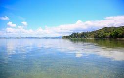 Opinión hermosa del agua con el fondo del cielo azul Playa de Whangarei, Imagen de archivo libre de regalías