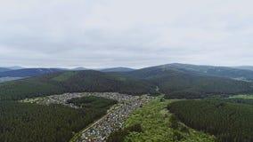 Opinión hermosa del aire de la situación de la ciudad entre las montañas verdes almacen de video