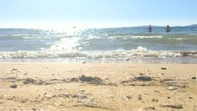 Opinión hermosa del mar con dos personas irreconocibles que se bañan almacen de metraje de vídeo