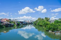 Opinión hermosa del paisaje del hogar de la costa o de la ciudad vieja situada al lado del río con el cielo azul en el fondo en e imagen de archivo