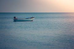 Opinión hermosa del paisaje marino del barco de pesca que flota en el mar con la luz de la puesta del sol en el fondo imagen de archivo