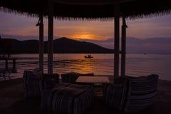Opinión hermosa del paisaje marino del barco de pesca que flota en el mar con la luz de la puesta del sol en el fondo en el tiemp foto de archivo libre de regalías