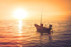 Opinión hermosa del paisaje marino el barco de pesca que flota en el mar con la luz de la puesta del sol en el fondo foto de archivo