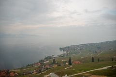 Opinión hermosa del panorama de la pequeña ciudad y del lago geneva en Suiza con el fondo del cielo nublado fotografía de archivo libre de regalías