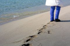 Opinión horizontal Person Walking en la arena que hace huellas encendido imágenes de archivo libres de regalías