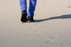 Opinión horizontal Person Walking en la arena que hace huellas encendido imagen de archivo