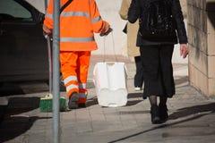 Opinión horizontal un basurero Walking en la calle al lado de un Woma fotos de archivo
