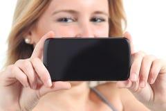 Opinión horizontal una mujer que muestra una pantalla negra del smartphone Imagen de archivo