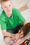 Opinión inclinada el muchacho con la pintura en las piernas y las manos Foto de archivo libre de regalías