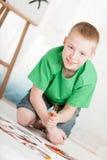 Opinión inclinada el muchacho que se arrodilla en la pintura Fotos de archivo