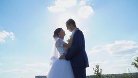 Opinión inferior sobre besar a recienes casados en los rayos del sol almacen de video