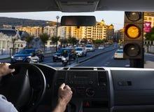 Opinión interior del coche de un semáforo anaranjado Fotos de archivo