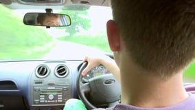 Opinión interior el adolescente que conduce el coche almacen de video