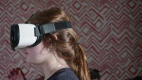 Opinión la muchacha caucásica en los vidrios de VR que intentan gobernar almacen de video