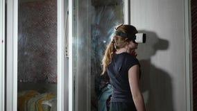 Opinión la muchacha caucásica en vidrios de VR Visión trasera delante del espejo almacen de metraje de vídeo