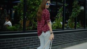 Opinión la mujer joven con el pelo y la mochila largos que camina cerca del café de la calle de la ciudad almacen de video