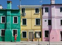 Opinión la mujer mayor con el vestido colorido que camina a través de fachada colorida en la isla de Burano cerca de Venecia fotos de archivo libres de regalías