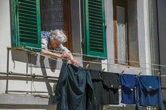 Opinión la mujer mayor que pone la ropa para secarse en la ventana en el ` Elsa de Colle di Val d imagen de archivo
