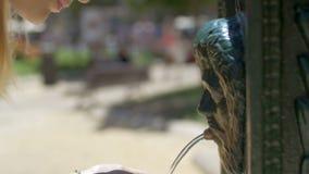 Opinión la mujer rubia joven en lentes de sol negros que bebe de la fuente pública vieja, Valencia, España almacen de video