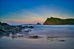 Opinión larga de la exposición de rocas, de la puesta del sol, de las montañas y del cielo coloreado multi imagen de archivo