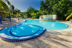 opinión los argumentos del hotel con la piscina de invitación agradable y la gente en fondo en jardín tropical Imagen de archivo