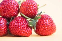 Opinión madura de la macro de la fresa Bayas frescas rojas con las hojas verdes en fondo amarillo Foto del campo de la profundida Imagen de archivo