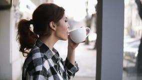 Opinión magnífica de las muchachas que se coloca cerca de las ventanas Consumición de un té con una taza blanca Vista lateral Fon almacen de video