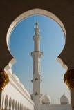 Opinión magnífica del alminar de la mezquita de Abu Dhabi a través de la arcada Imagen de archivo libre de regalías