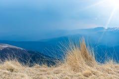 Opinión natural del paisaje de montañas, hierba y rayos fuertes del sol, fondo hermoso para los diseños y tarjetas Paisaje tempra fotos de archivo
