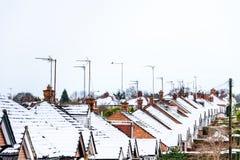 Opinión nublada del invierno del día de la fila de casas colgantes inglesas típicas debajo de la nieve en Northampton fotografía de archivo