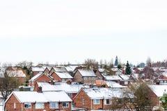 Opinión nublada del invierno del día de la fila de casas colgantes inglesas típicas debajo de la nieve en Northampton foto de archivo libre de regalías