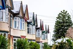 Opinión nublada del invierno del día de la fila de casas colgantes inglesas típicas debajo de la nieve en Northampton imagen de archivo libre de regalías