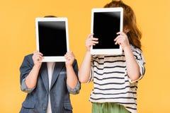 opinión obscurecida los niños que sostienen las tabletas con las pantallas en blanco fotografía de archivo