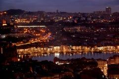 Opinión panorámica de la noche del centro de ciudad de Oporto y del río del Duero con las reflexiones de las luces en el agua Imágenes de archivo libres de regalías
