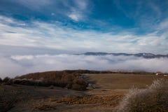 Opinión panorámica de las montañas y de las colinas del paisaje pueblos y niebla inminente fotografía de archivo