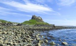 Opinión panorámica del castillo de Lindisfarne de una playa y de un agua azul, isla santa, Northumberland de la roca imagen de archivo