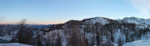 Opinión panorámica del invierno maravilloso sobre las montañas nevosas en cielo azul de la puesta del sol Imágenes de archivo libres de regalías