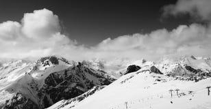 Opinión panorámica sobre cuesta del esquí y las montañas nubladas en el día agradable del sol Foto de archivo libre de regalías