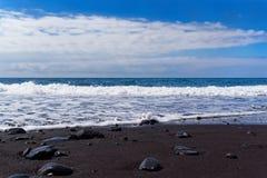 Opinión panorámica sobre una playa negra de la arena contra el cielo azul fotos de archivo libres de regalías