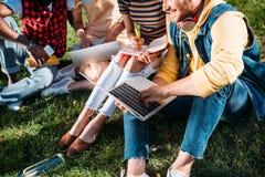 opinión parcial el grupo interracial de estudiantes con los ordenadores portátiles y los cuadernos que estudian en verde foto de archivo