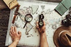 opinión parcial el hombre con el compás en el tablero de la mesa con el mapa, la lupa, la cámara de la foto y el sombrero foto de archivo