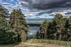 Opinión pintoresca sobre el lago y el bosque en el tiempo de la tarde momentos antes de la puesta del sol Cielo y nubes reflejado Imagen de archivo libre de regalías
