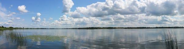 Opinión pintoresca sobre el lago y el bosque en el tiempo de la tarde momentos antes de la puesta del sol Cielo y nubes reflejado Fotos de archivo