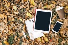 Opinión plana de la endecha de las hojas de otoño, de la tableta, del teléfono y de la taza de papel de coffe Desde arriba con de Imagen de archivo libre de regalías