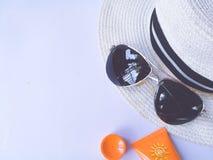 Opinión plana de la endecha de los accesorios del verano y del viaje Sombrero, vidrios de sol, protección poner crema del sunbloc imagenes de archivo