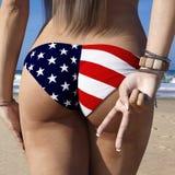 Opinión posterior de la parte trasera una hembra morena del ajuste que lleva un bañador del estilo de la bandera americana en una libre illustration