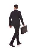 Opinión posterior un hombre de negocios que recorre con la cartera Foto de archivo libre de regalías