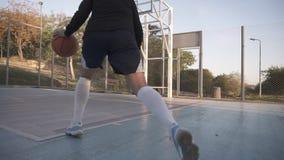 Opinión rara un jugador de básquet de la chica joven que entrena y que ejercita al aire libre en la corte local - 26 de abril: Ch almacen de video