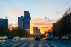 Opinión romántica de la puesta del sol y de la calle con los coches en el camino Moscú imagenes de archivo